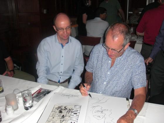 Dave Gibbons sidder og nummerere, signere og tegner i mit eksemplar af Watchmen Artifact Edition.